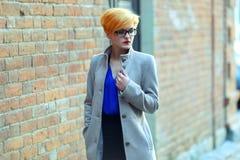 Schönes junges Mädchen in einem Mantel auf der Straße Lizenzfreie Stockfotos