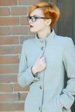 Schönes junges Mädchen in einem Mantel auf der Straße Stockbild
