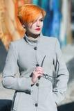 Schönes junges Mädchen in einem Mantel auf der Straße Stockbilder