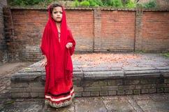 Schönes junges Mädchen in einem roten Kleid vor einer Zeremonie Stockbild