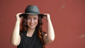 Schönes junges Mädchen in einem schwarzen Hut des Strohs, der mit dem roten Haar lächelnd, ein Gesicht lachend und machend spielt stock video