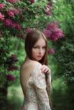 Schönes junges Mädchen in einer blühenden Flieder Stockfotos