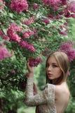 Schönes junges Mädchen in einer blühenden Flieder Stockfoto