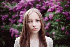 Schönes junges Mädchen in einer blühenden Flieder Stockfotografie