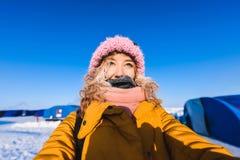 Schönes junges Mädchen in einer des Gelbs Jacke unten und in einer rosa Strickmütze mit dem roten Haar in einem Frost im Hintergr Lizenzfreies Stockbild