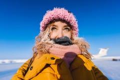 Schönes junges Mädchen in einer des Gelbs Jacke unten und in einer rosa Strickmütze mit dem roten Haar in einem Frost im Hintergr Lizenzfreie Stockfotografie