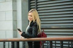 Schönes junges Mädchen in einer schwarzen Jacke draußen lizenzfreies stockbild