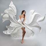 Schönes junges Mädchen in fliegendem weißem Kleid Stockfotos