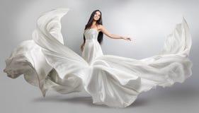 Schönes junges Mädchen in fliegendem weißem Kleid Flüssiges Gewebe Helles weißes Stofffliegen Stockbild