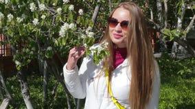 Schönes junges Mädchen flirtet das Lächeln und wirft für ein Foto in den Blumen des Baums auf stock video
