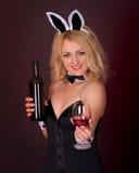 Schönes junges Mädchen gekleidet als Kaninchen mit Wein Stockbilder
