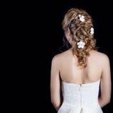 Schönes junges Mädchen im Bild der Braut, schöne Hochzeitsfrisur mit Blumen in ihrem Haar, Frisur für Braut Stockfotos
