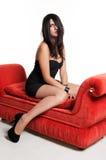 Schönes junges Mädchen im schwarzen Kleid auf rotem Sofa Stockbild