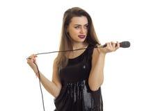 Schönes junges Mädchen im schwarzen Kleid hält ein Mikrofon in ihrer Hand und blickt in Richtung Stockfoto