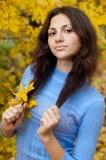 Schönes junges Mädchen ist bis zum einem Herbsttag Stockfotografie