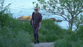 Schönes junges Mädchen klettert einen Weg auf einem Hügel nahe dem Meer stock video footage