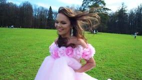 Schönes junges Mädchen laufen in Hochzeitskleid an Bäume im Freien Rosarosen-Blumenkleid im Wald stock footage