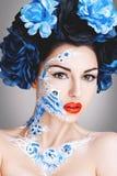 Schönes junges Mädchen mit blauen Blumen lizenzfreie stockfotos