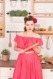 Schönes junges Mädchen mit Blume in ihrem Haar, das zu Hause im roten Stift herauf Tupfenkleid in der Küche aufwirft stockfotografie