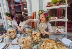 Schönes junges Mädchen mit Blumen im Haar, das Plätzchen, Kuchen eines backery während eines Straßenfests verkauft Lizenzfreie Stockbilder