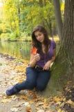 Schönes junges Mädchen mit dem dunklen Haar im Park Lizenzfreies Stockfoto