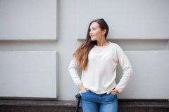 Schönes junges Mädchen mit dem langen braunen Haar beim Reiten des Rollers gestoppt auf den Hintergrund der grauen Wand Sie wird  Stockfotografie