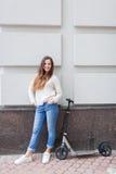 Schönes junges Mädchen mit dem langen braunen Haar beim Reiten des Rollers gestoppt auf den Hintergrund der grauen Wand Sie wird  Lizenzfreie Stockfotos