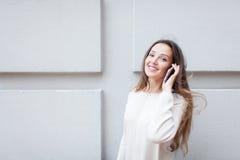 Schönes junges Mädchen mit dem langen braunen Haar beim Reiten des Rollers gestoppt, um einen Freund am Telefon auf dem Hintergru Lizenzfreies Stockfoto