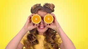 Sch?nes junges M?dchen mit dem Legen der Aufstellung mit Orangen und des l?chelnden Schauens in die Kamera auf einen gelben Hinte stock video footage