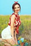 Schönes junges Mädchen mit dem perfekten verlockenden Lächeln, welches die rote Bluse, die weißen kurzen Hosen und das Stirnband  lizenzfreies stockfoto
