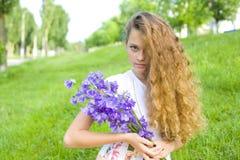 Schönes junges Mädchen mit einem Blumenstrauß der Blumen Stockfotografie