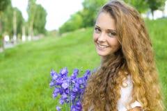 Schönes junges Mädchen mit einem Blumenstrauß der Blumen Lizenzfreies Stockbild