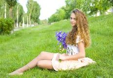 Schönes junges Mädchen mit einem Blumenstrauß der Blumen Stockbilder