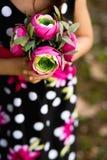 Schönes junges Mädchen mit einem Blumenstrauß der Blumen Stockfoto