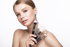 Schönes junges Mädchen mit einem hellen natürlichen Make-up, Bürsten für Kosmetik und französische Maniküre Schönes lächelndes Mä stockbilder