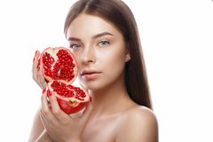Schönes junges Mädchen mit einem hellen natürlichen Make-up und perfekte Haut mit Granatapfel in ihrer Hand Schönes lächelndes Mä stockfotografie