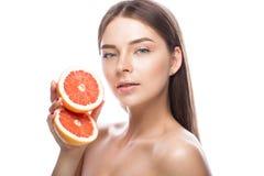 Schönes junges Mädchen mit einem hellen natürlichen Make-up und perfekte Haut mit Pampelmuse in ihrer Hand Schönes lächelndes Mäd lizenzfreie stockbilder