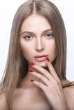 Schönes junges Mädchen mit einem hellen natürlichen Make-up und roten Nägeln Stockfoto