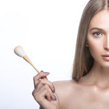Schönes junges Mädchen mit einem hellen natürlichen Make-up und Schönheitswerkzeugen in der Hand Lizenzfreies Stockfoto