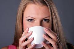 Schönes junges Mädchen mit einer Kaffeetasse Lizenzfreie Stockfotografie