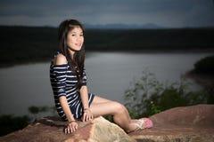 Schönes junges Mädchen mit Fluss- und Himmelhintergrund Lizenzfreie Stockfotografie