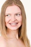 Schönes junges Mädchen mit Haltern auf Zähnen Stockfoto
