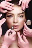 Schönes junges Mädchen mit natürlichem nacktem Make-up mit kosmetischen Werkzeugen in den Händen Schönes lächelndes Mädchen lizenzfreies stockbild