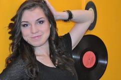 Schönes junges Mädchen mit Platten auf einem gelben Hintergrund Lizenzfreie Stockfotografie
