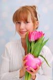 Schönes junges Mädchen mit rosa Tulpen und Herzen Lizenzfreies Stockfoto