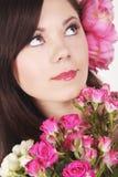 Schönes junges Mädchen mit rosafarbenen Blumen Stockfoto