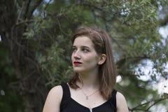 Schönes junges Mädchen mit rotem Lippenstift und blaue Augen im Halbprofil stockfoto