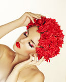 Schönes junges Mädchen mit roten Blumen stockfotos