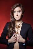 Schönes junges Mädchen mit schönem stilvollem teurem Schmuck, Halskette, Ohrringe, Armband, Ring, filmend im Studio Stockfoto
