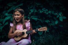 Schönes junges Mädchen mit Ukulele stockfotos